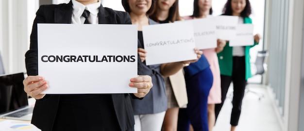 Grupa przedsiębiorców w ubrania biznesowe ustawić wiersz i trzymając papierowy baner z gratulacjami słownymi i pokaż do kamery. koncepcja powitania i uznania za sukces w pracy lub pracy w firmie.