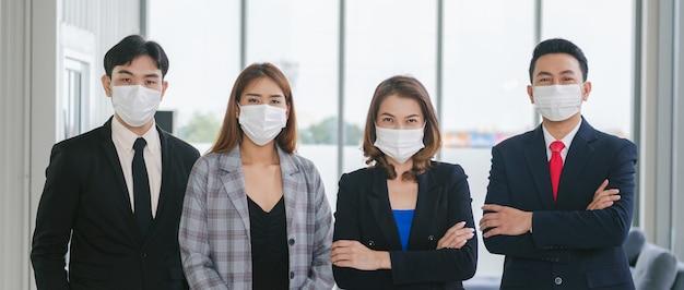 Grupa przedsiębiorstw noszących maski chirurgiczne stojących patrzeć na aparat w biurze. koncepcja opieki zdrowotnej chroni przed wirusami corona-covid19