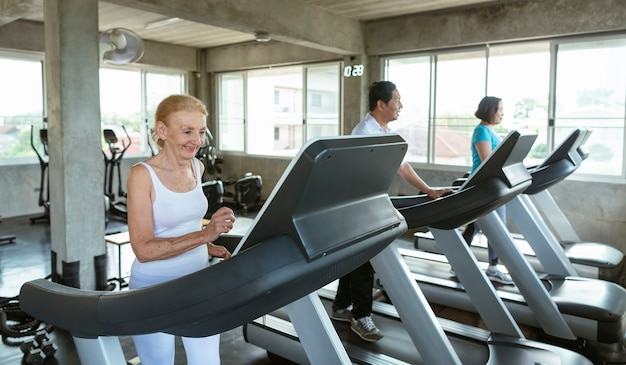 Grupa przyjaciel starszego biegacza w siłowni fitness uśmiechnięty i szczęśliwy. zdrowy styl życia w podeszłym wieku.