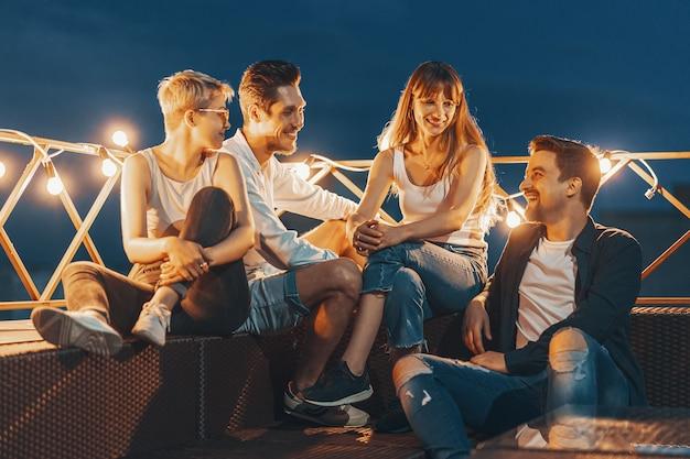 Grupa przyjaciele cieszy się outdoors przy dachem