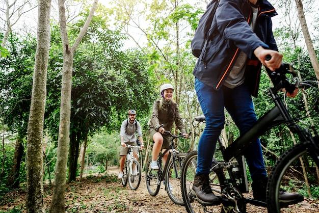 Grupa przyjaciele jedzie rower górskiego w lesie wpólnie