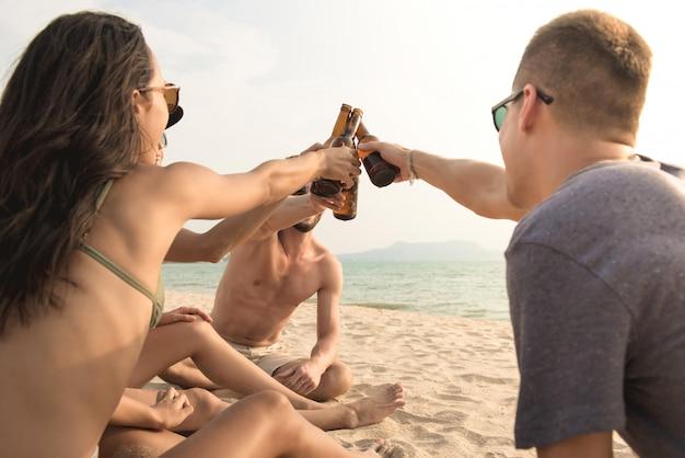 Grupa przyjaciele ma przyjęcia claging piwne butelki przy plażą