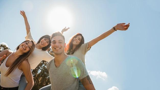 Grupa przyjaciele podnosi ręki na nieba tle