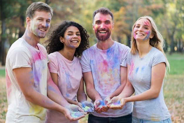 Grupa przyjaciele pozuje podczas gdy trzymający farbę