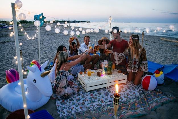 Grupa przyjaciele robi przyjęciu na plaży przy zmierzchu czasem