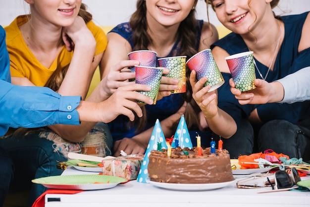Grupa przyjaciele wznosi toast szkła sok na przyjęciu urodzinowym