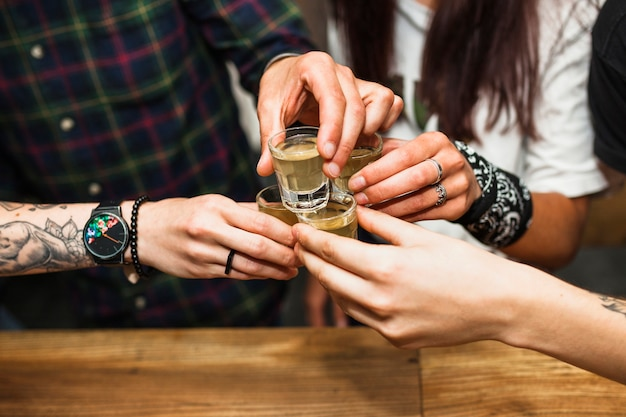 Grupa przyjaciele wznosi toast tequila strzał