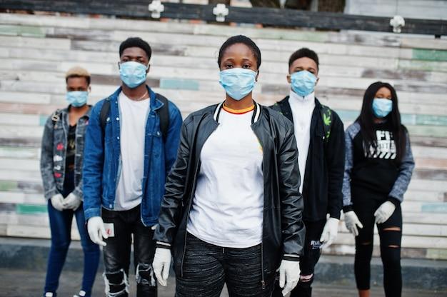 Grupa przyjaciół afrykańskich nastolatków noszących maski medyczne chroni przed infekcjami i chorobami kwarantanny wirusa koronawirusa.
