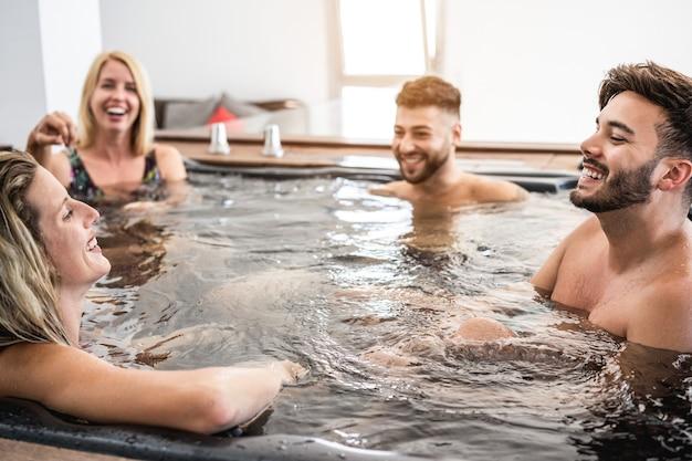 Grupa przyjaciół bawi się i relaksuje w wannie z hydromasażem na prywatnej imprezie w wiosce