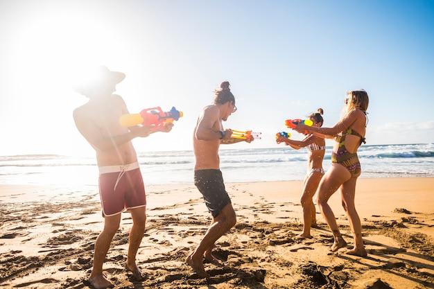 Grupa przyjaciół bawi się na plaży z pistoletami na wodę podczas szczęśliwych wakacji - koncepcja młodych ludzi cieszących się przyjaźnią i zabawą na świeżym powietrzu, bawiąc się razem