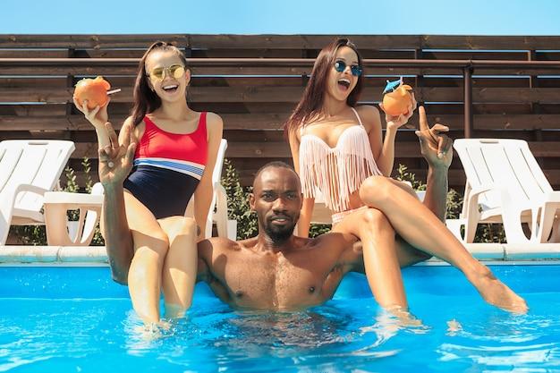 Grupa przyjaciół bawiąca się i relaksująca w basenie podczas letnich wakacji