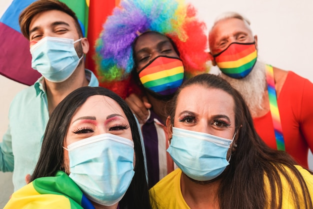 Grupa przyjaciół bawiąca się paradą lgbt robiąca selfie podczas epidemii koronawirusa