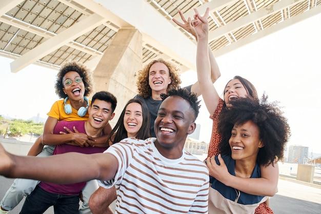 Grupa przyjaciół bawiących się w mieście, młodzi międzyrasowi studenci biorący koncepcję selfie z przyjacielem
