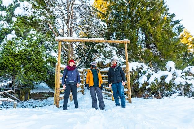 Grupa przyjaciół bawiących się w zaśnieżonym lesie w miejscowości oiartzun w penas de aya, gipuzkoa. kraj basków