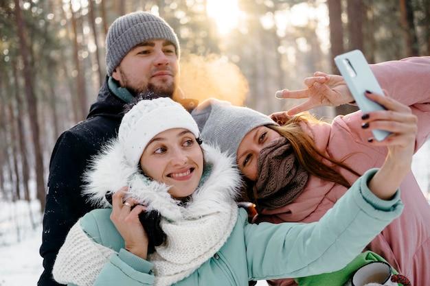 Grupa przyjaciół, biorąc selfie na zewnątrz w zimie