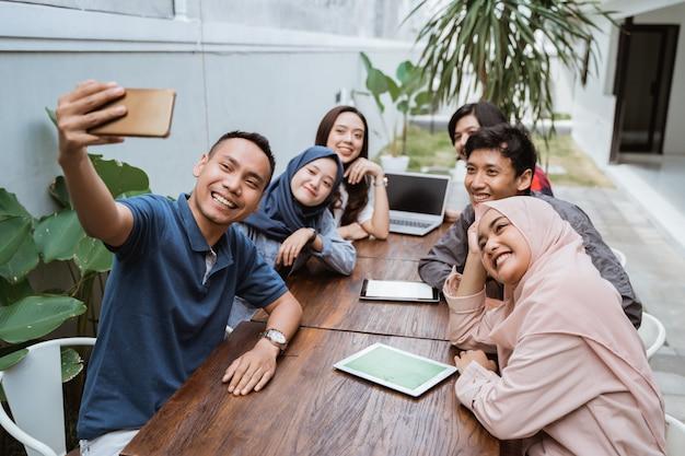 Grupa przyjaciół biura cieszyć się na spotkanie z selfie