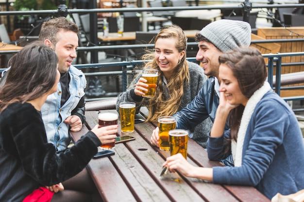 Grupa przyjaciół ciesząc się piwo w pubie w londynie
