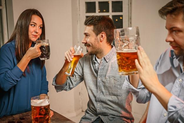 Grupa przyjaciół, ciesząc się wieczorne drinki z piwem