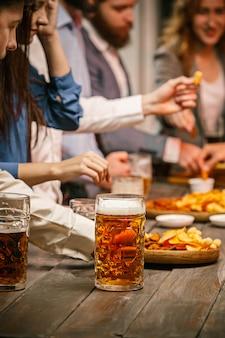 Grupa przyjaciół, ciesząc się wieczorne napoje z piwem