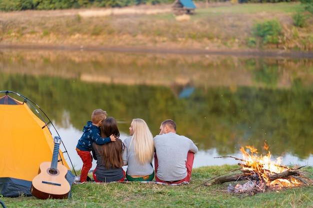 Grupa przyjaciół cieszy się widokiem, biwakując przy ognisku nad brzegiem rzeki