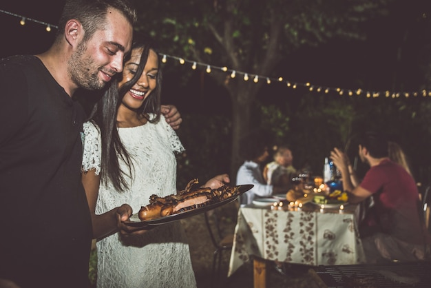 Grupa przyjaciół co grill na podwórku w czasie kolacji