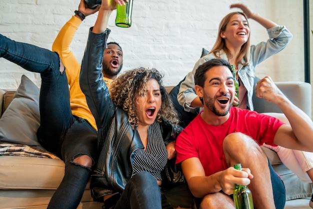 Grupa przyjaciół dobrze się bawi i pije piwo z butelki podczas wspólnego oglądania meczu.