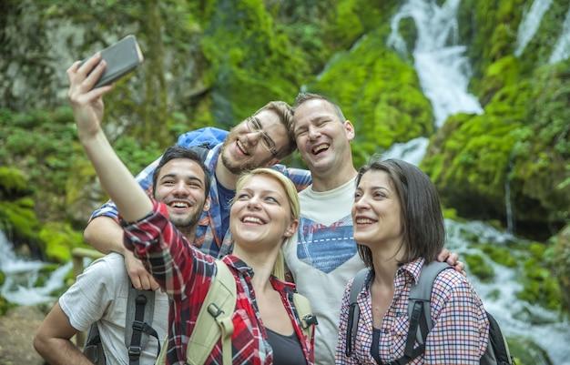 Grupa przyjaciół dobrze się bawi i robi selfie na łonie natury