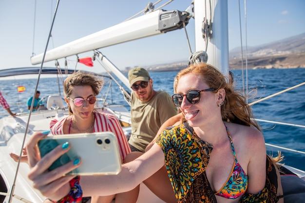 Grupa przyjaciół dwie kobiety i jeden mężczyzna robią sobie selfie podczas imprezy na łodzi szczęśliwi ludzie