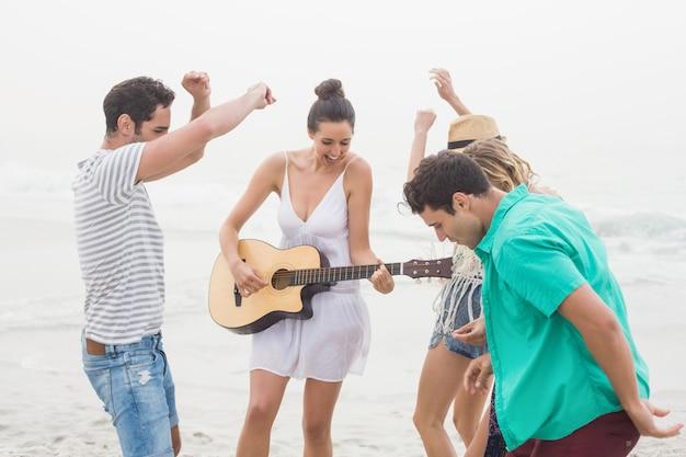 Grupa przyjaciół, gra na gitarze i taniec