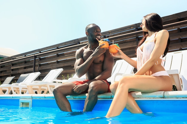 Grupa przyjaciół, grając i relaksując się w basenie podczas wakacji