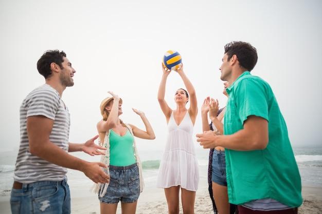 Grupa przyjaciół, grając w piłkę plażową
