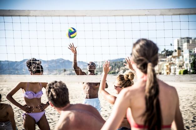 Grupa przyjaciół, grając w siatkówkę plażową.