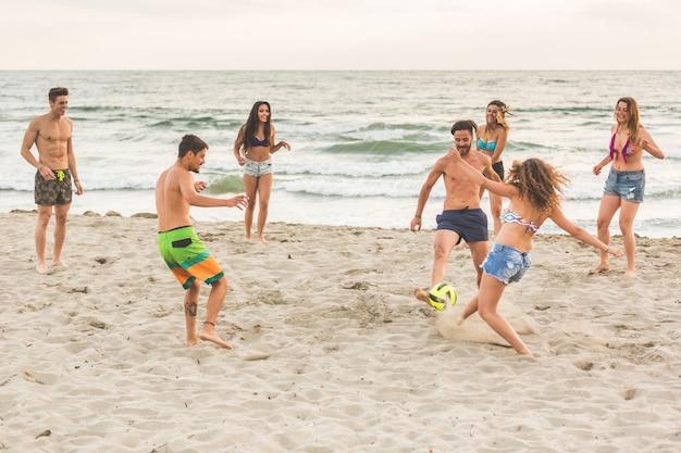 Grupa przyjaciół, grając z piłką na plaży