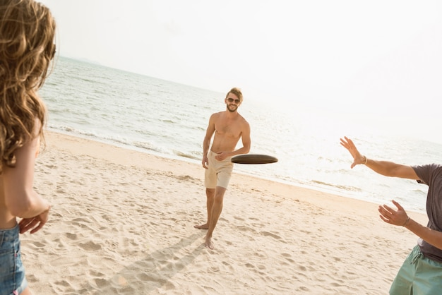 Grupa przyjaciół grających na szybowcowym dysku na plaży