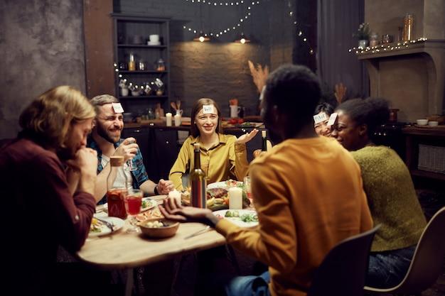 Grupa przyjaciół grających w zgadywanie podczas kolacji