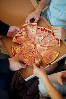 Grupa przyjaciół je pizzę