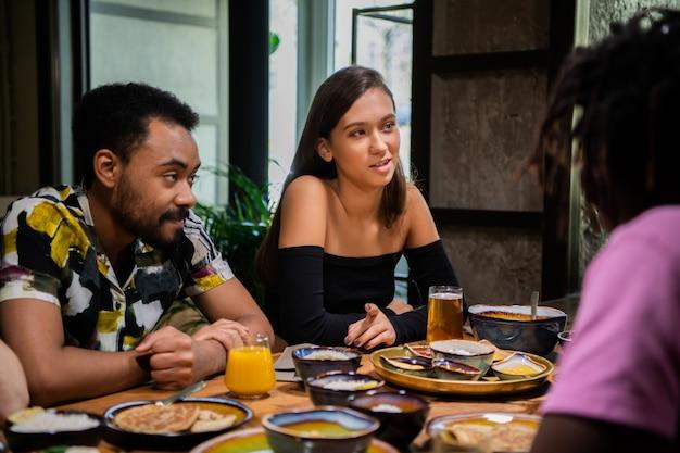 Grupa przyjaciół jedzących i rozmawiających
