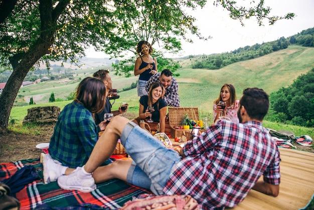 Grupa przyjaciół jedzenia w naturze