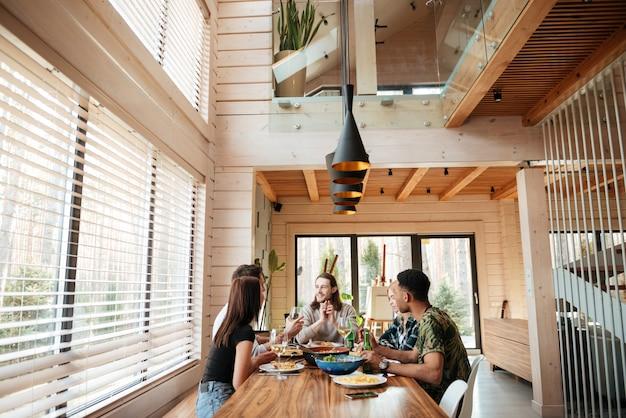 Grupa przyjaciół, jedzenie i rozmawianie w kuchni