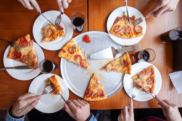 Grupa przyjaciół, jedzenie włoskiej pizzy