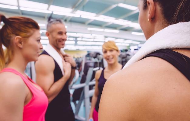 Grupa przyjaciół kobiet rozmawia z osobistym trenerem centrum fitness. selektywne skupienie się na ramieniu z powrotem dziewczyny.