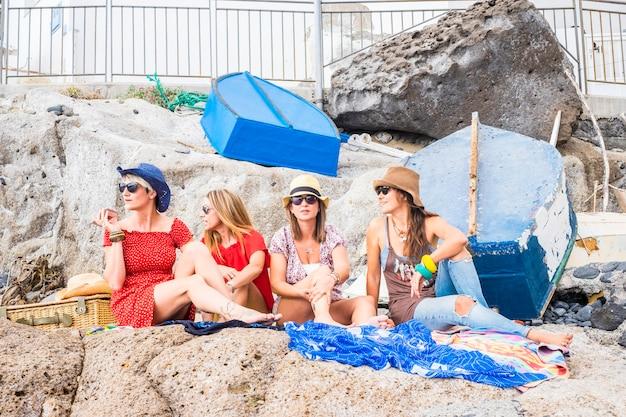 Grupa przyjaciół kobiet siedzących na skałach w pobliżu morza i cieszących się wakacjami i rekreacją na świeżym powietrzu, relaksując się w przyjaźni. szczęśliwi ludzie, cztery kobiety pozostają razem w letnim słońcu