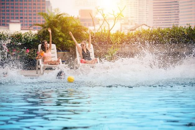 Grupa przyjaciół korzysta z zabawy przy basenie i wskakuje do basenu w lecie