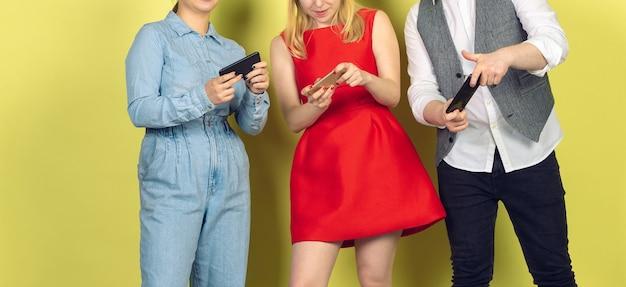 Grupa przyjaciół korzystających ze smartfonów mobilnych. uzależnienie nastolatków od nowych trendów technologicznych. ścieśniać.