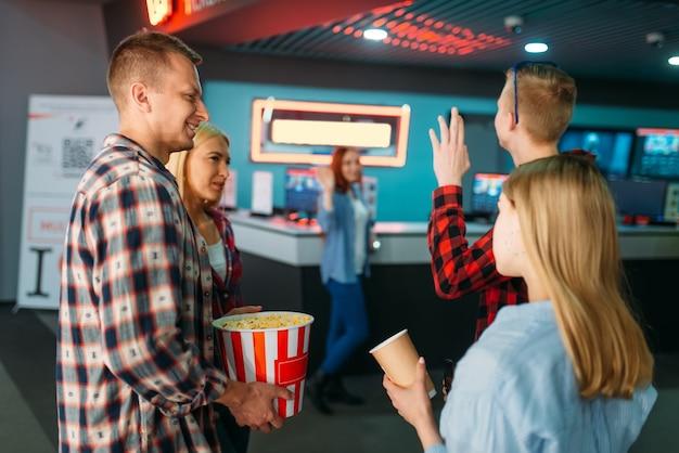 Grupa przyjaciół kupuje bilety w kasie kina. młodzież płci męskiej i żeńskiej czeka w kinie, rozrywkowy styl życia