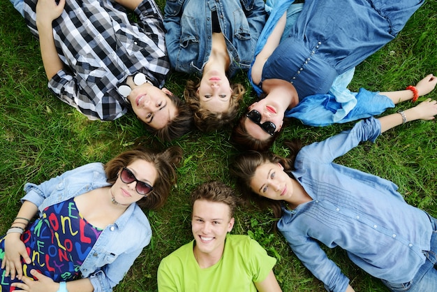 Grupa przyjaciół, leżąc na łące
