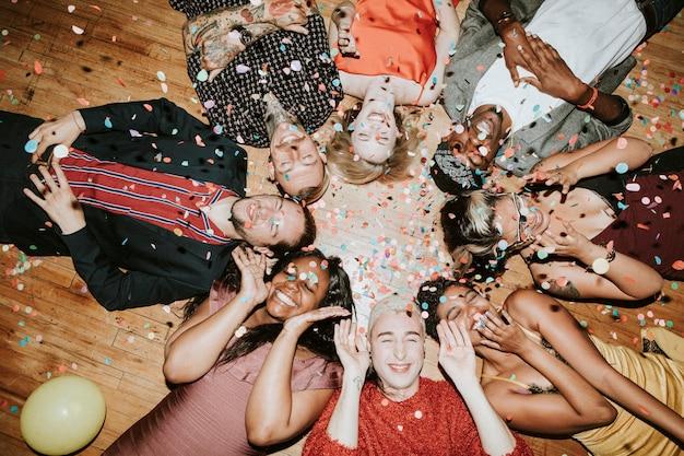 Grupa przyjaciół leżąca na podłodze na imprezie