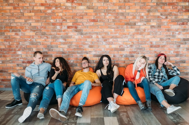 Grupa przyjaciół lub kolegów siedzących na workach z fasolą. milenijny styl życia