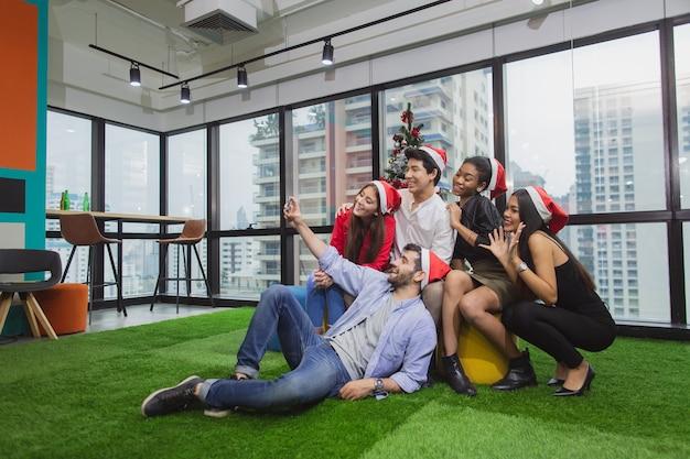 Grupa przyjaciół lub kolegów z różnych narodowości bawi się przyjęciem świątecznym w biurze roboczym
