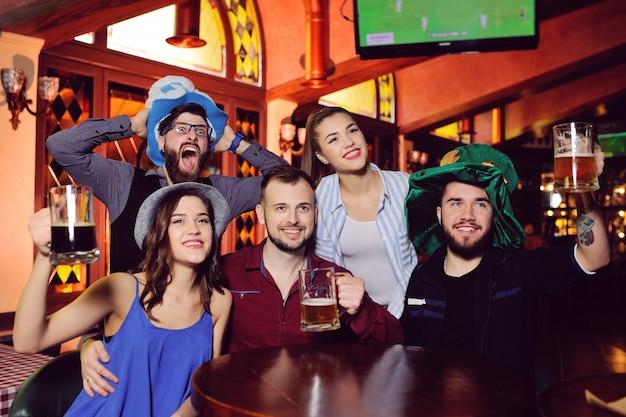 Grupa przyjaciół lub towarzystwo przyjaciół - młodzi chłopcy i dziewczęta trzymający szklanki piwa, oglądający piłkę nożną, śmiejący się i uśmiechający się do baru podczas festiwalu oktoberfest